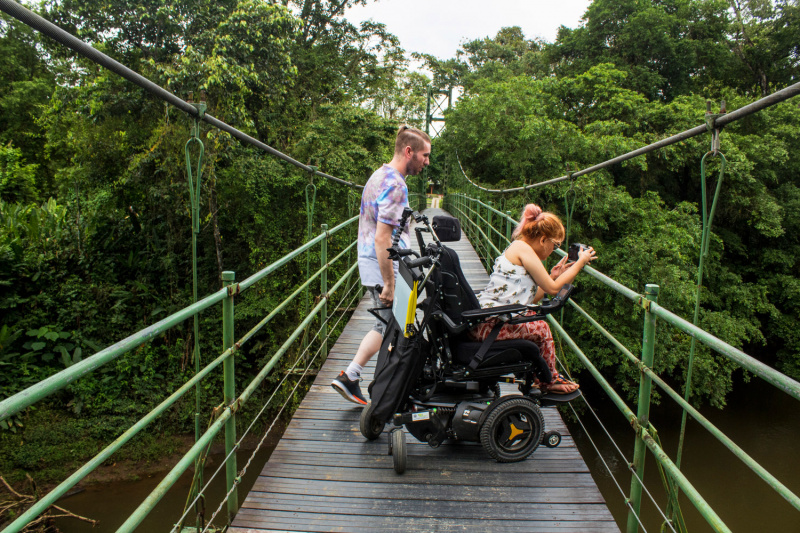 Wheel the World traveler and companion peer over the endge a rainforest bridge looking to the ravine below.