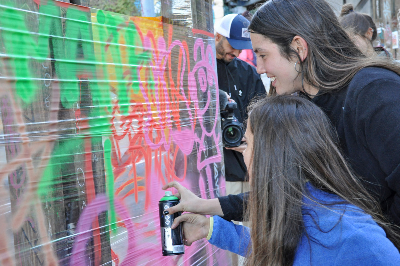 Visitors spray paint a wall while on the Street Art Experience tour.