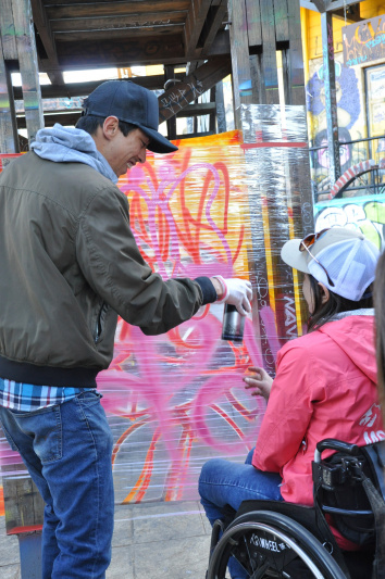 Wheel the World guide hands visitor on a wheelchair a can of spray paint.