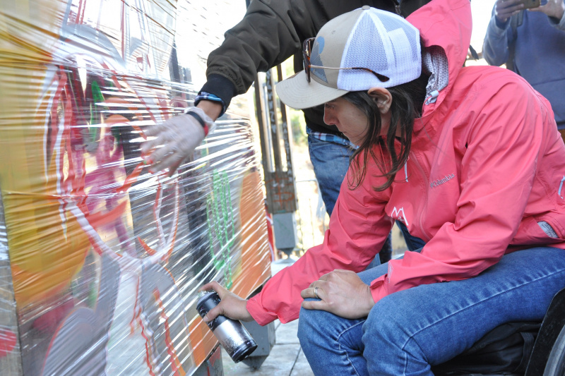 Visitor spray paints while on the Street Art Experience tour.
