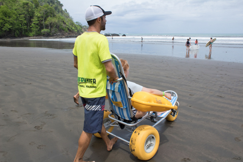 A traveler uses the amphibious wheelchair to traverse the beach and head to the water