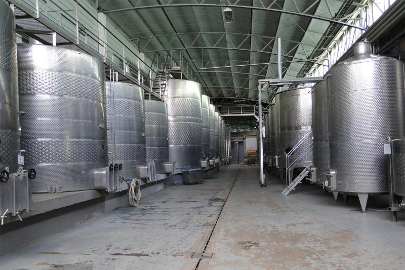 Travelers navigate through steel fermentation tanks.