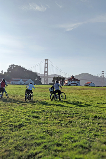 Travelers use bikes to explore Crissy Feilds near the Golden Gate Bridge
