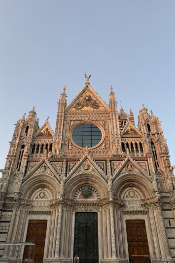 Piazza del Duomo with towering exterior and ornate design features.