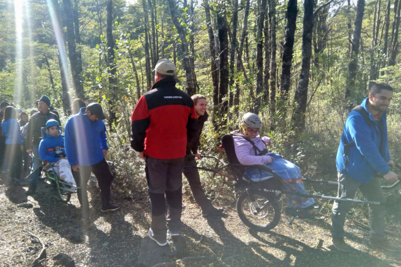 Group on the Pioneros trekking tour make their way up a mountain using the Jolette wheelchair