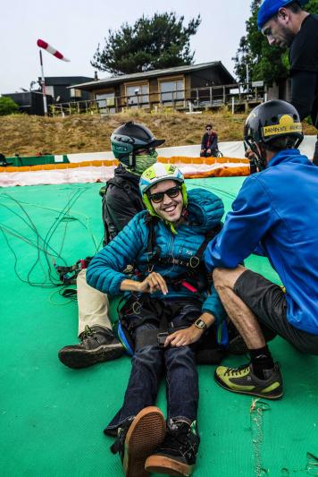 Traveler smiles after paragliding trip over Maitencillo.