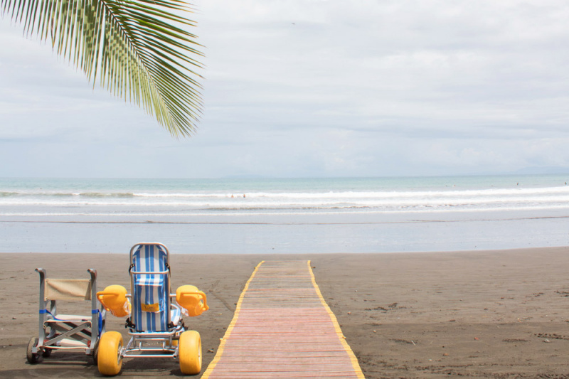 An amphibious chair sits next to an accessible pathway leading to Jaco Beach waters