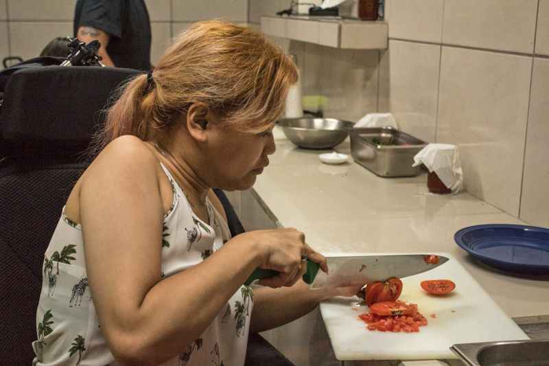 Guest who uses a wheelchair cuts tomatoes during cooking class