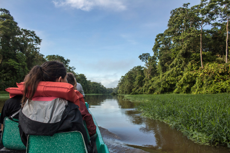 Guests with life vests enjoy animal watching on the Tortuguero tour