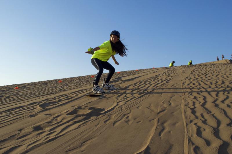 Woman surfs the dunes of Iquique