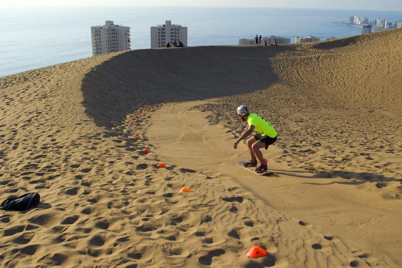 Man surfs the dunes of Iquique