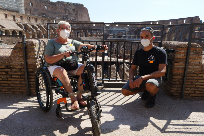 Woman on wheelchair and Wheel the World staff pose infront of Colosseum ruins