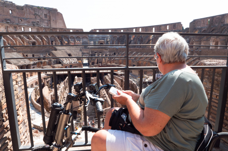 Woman on a wheelchair explores the Colosseum ruins