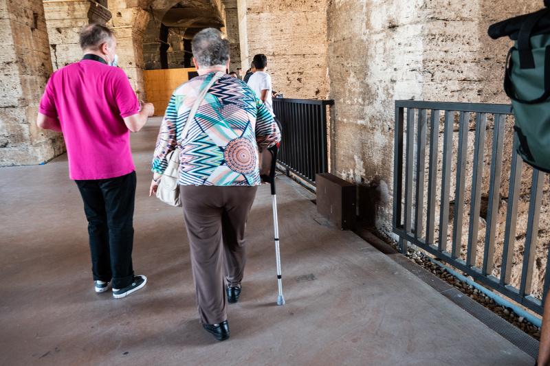 Couple using walking sticks enjoys tour of Colosseum ruins