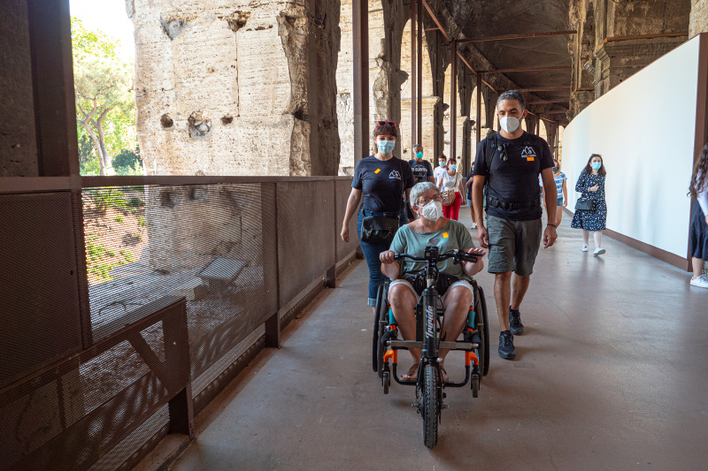 Woman on wheelchair and Wheel the World Staff view walk on smooth vinyl floor on the Colosseum property