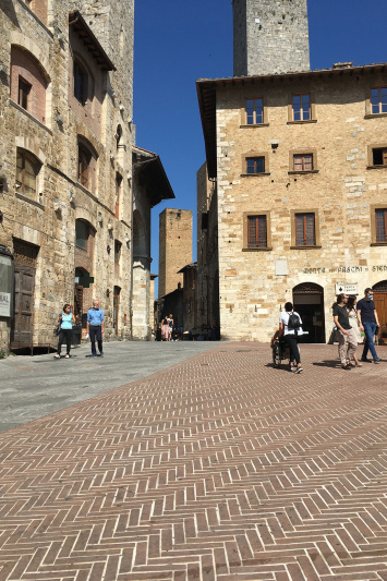 Street view of San Gimignano's historic buildings and tiled stone streets