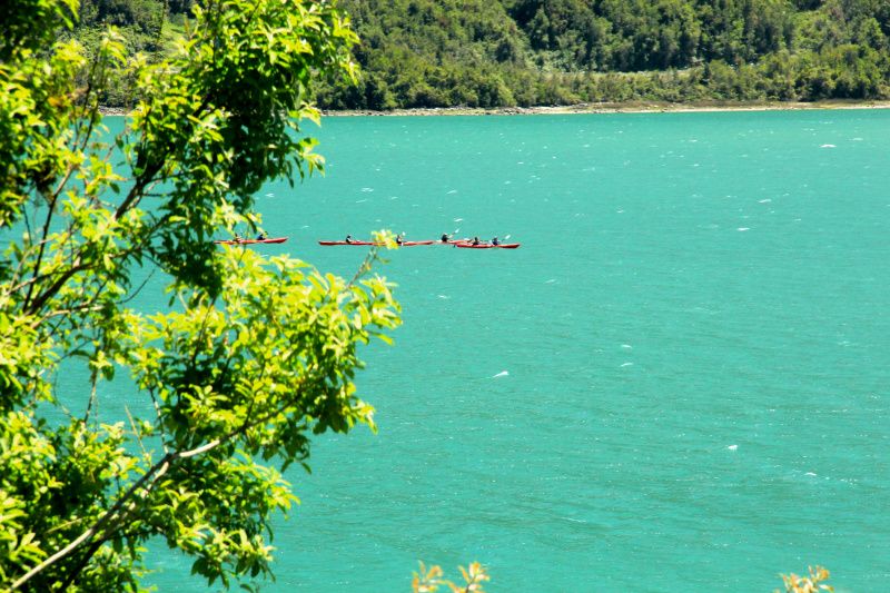 A group of kayakers seen in the distance on the turquoise water of Lake Caburgua.