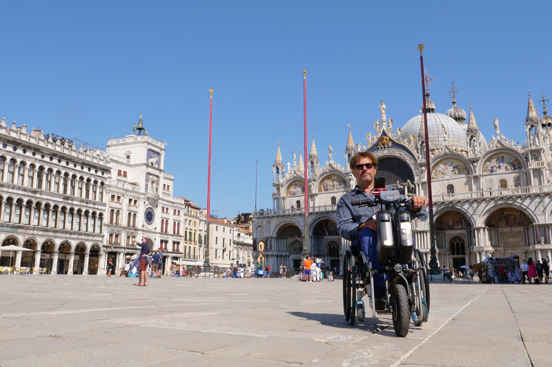 A man in a wheelchair poses in front of the historic St Mark's square