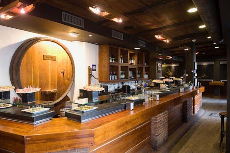 The wooden bar inside Sagardi restaurant, with plates of pintxos.