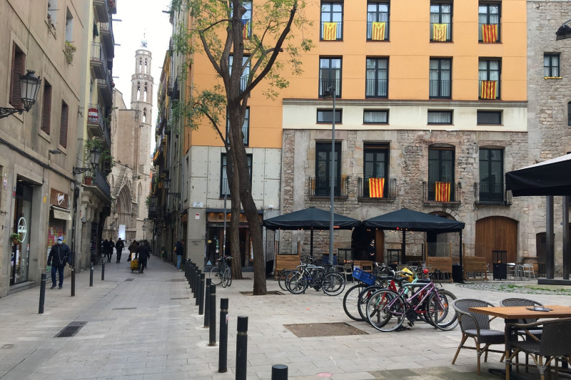 Plaça de Jacint Reventós square, the meeting point for the tour, a square with restaurant tables and a bike station.
