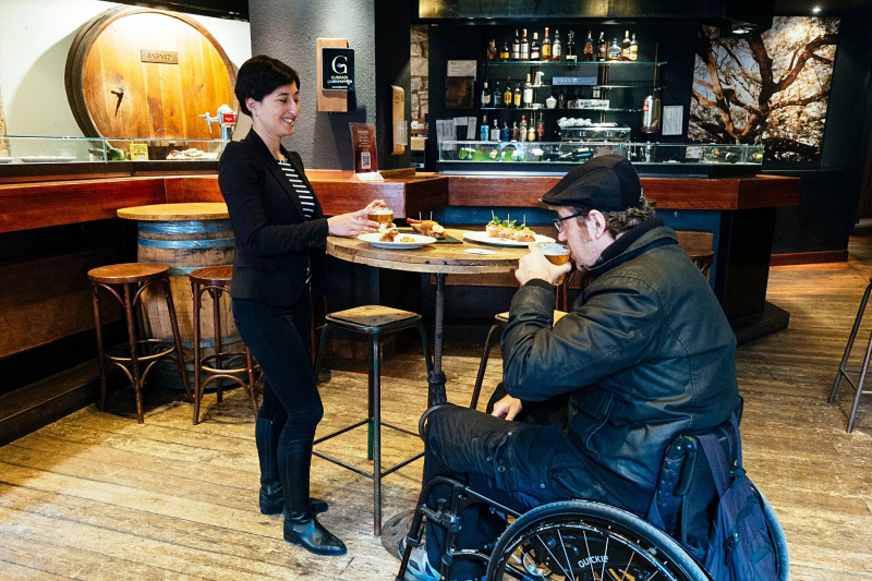 A man in a wheelchair and a woman inside Sagardi, by a table with pintxos on.