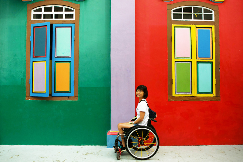 A woman in a wheelchair sits sideways smiling at the camera in front of a bright colored wall.