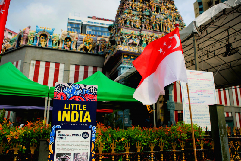A sign reads Little India Heritage Trail in front of a Hindu temple.