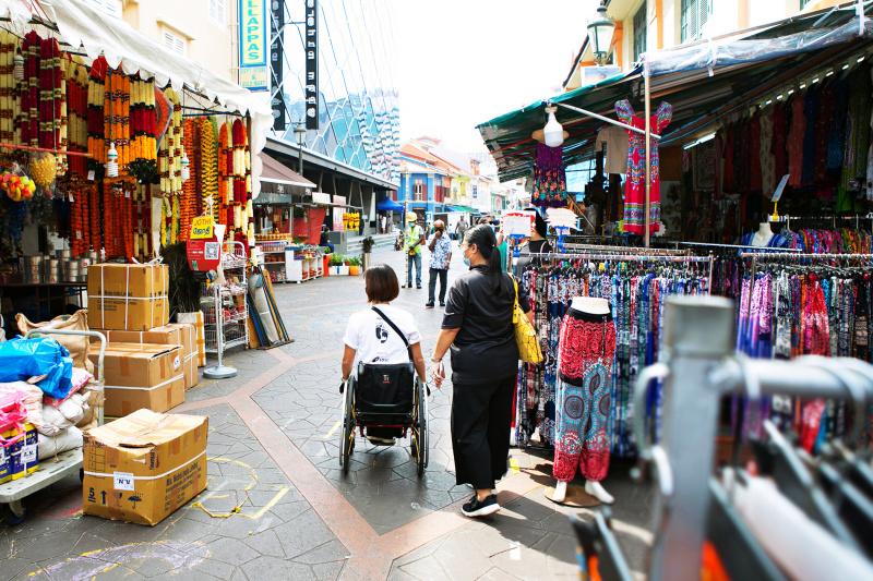 Two women, one in a wheelchair, walk through a market admiring souvenirs.