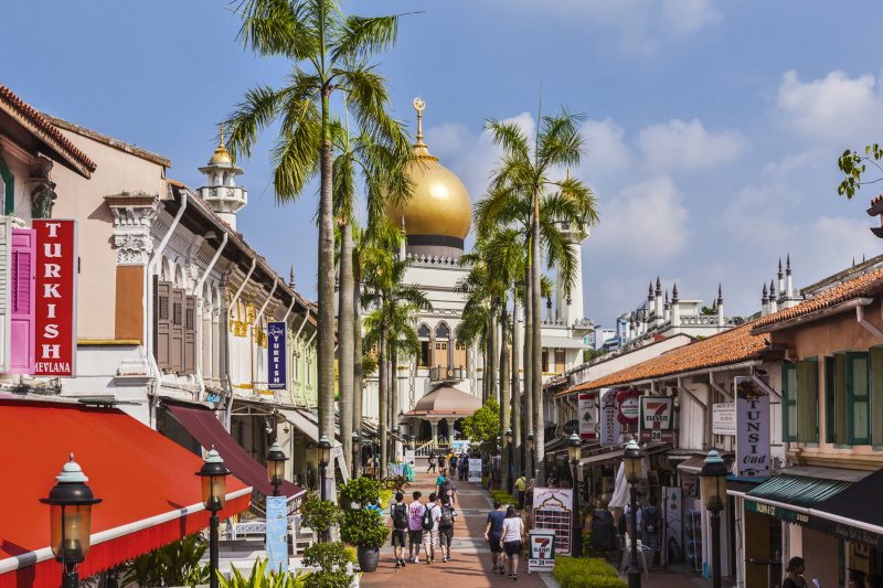 Colorful shops line the street leading to the Kampong Mosque with a gold dome.