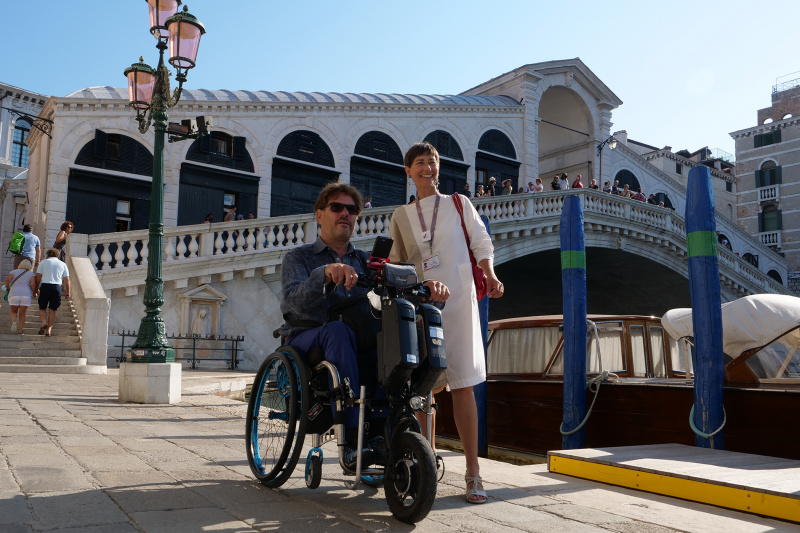 Tour guide and attendant use a wheelchair to navigate Venice's city streets
