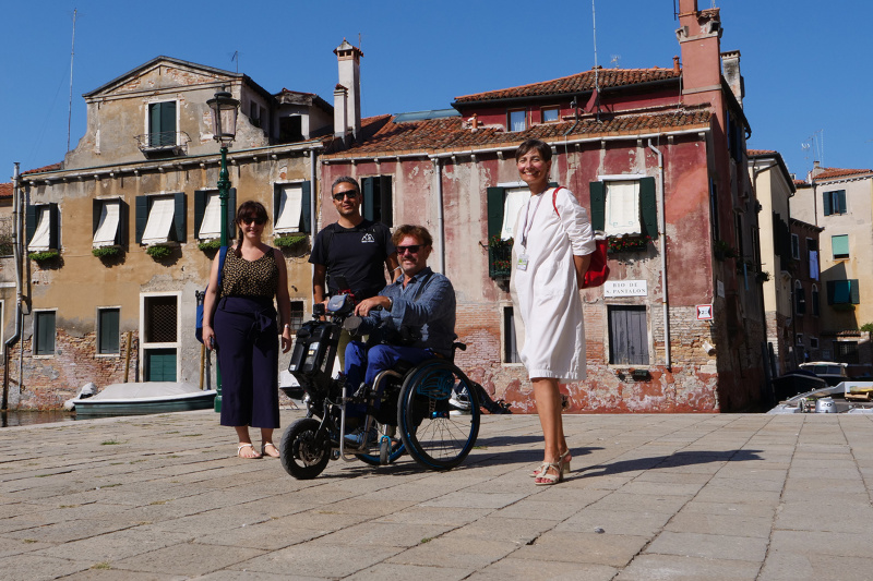 Tour participants and guide navigate Campo San Rocco's cobblestone streets and canals using wheelchair and other mobility related devices