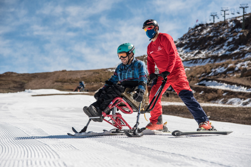 An instructor pushed a skiier sitting on adaptive equipment.