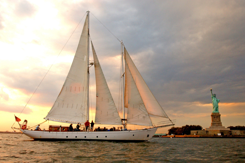 A large white sailing boat in front of the Statue of Liberty