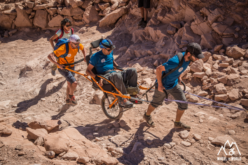 A group of friends travers desert lands using a joëlette wheelchair, one of them sits on it, and two of them carry the chair working as a team.