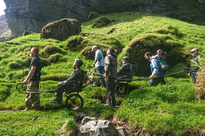 A group of friends travers uneven lands using a joëlette wheelchair