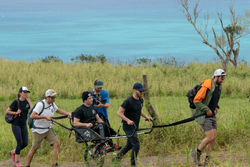A group of friends travers uneven lands using a joëlette wheelchair, one of them sits on it, and two of them carry the chair working as a team.