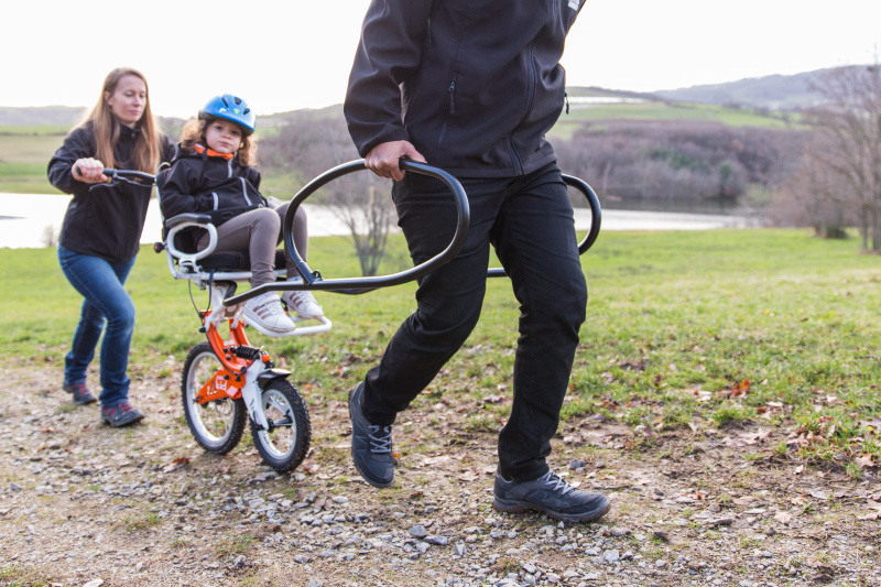 A father is steering his son around the park
