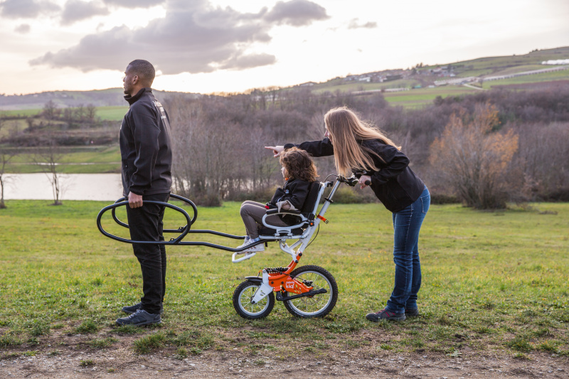 A joëlette kids wheelchair is a single wheeled wheelchair with support and steering bars in the front and back.