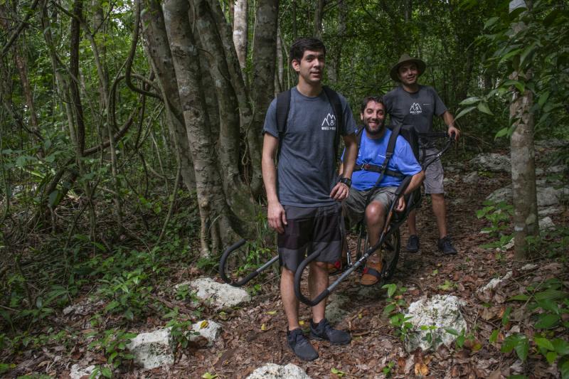 A group of friends travers uneven Rivera Maya lands using a joëlette wheelchair