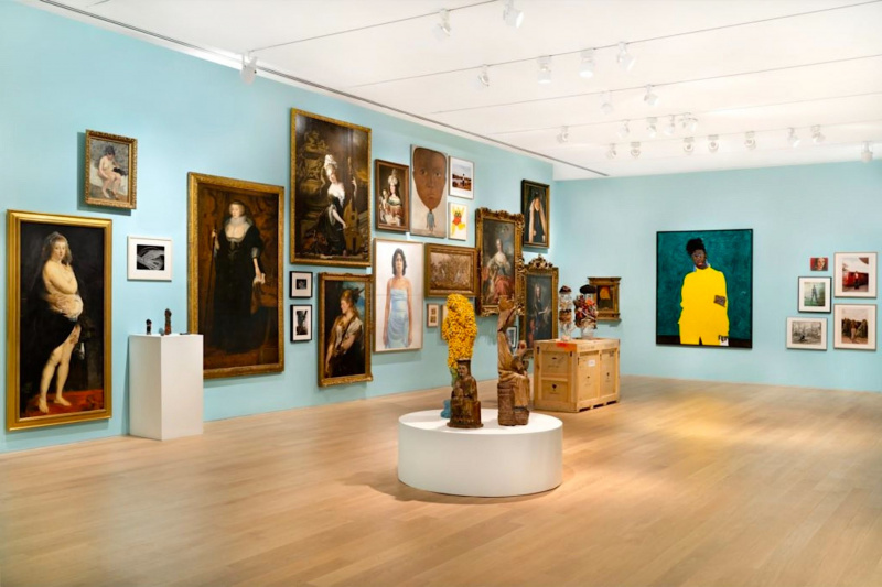 A gallery in the Bass Museum of Art with paintings and sculptures. The floor is tiled and the gallery is spacious.