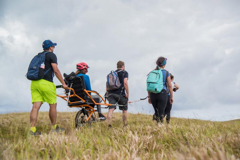 A group of friends travers uneven Easter Island lands using a joëlette wheelchair