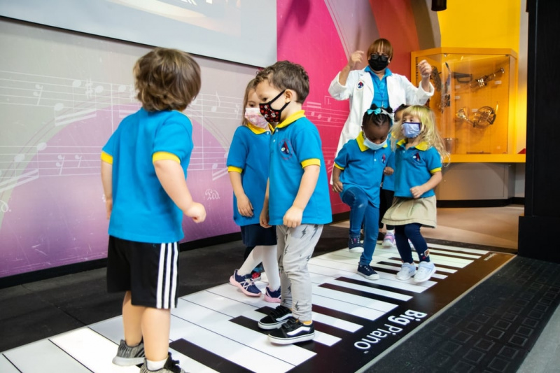 Children dancing on a giant piano keyboard on the ground.