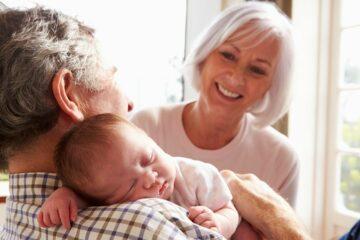 opa en oma op kraamvisite houden pasgeboren baby vast