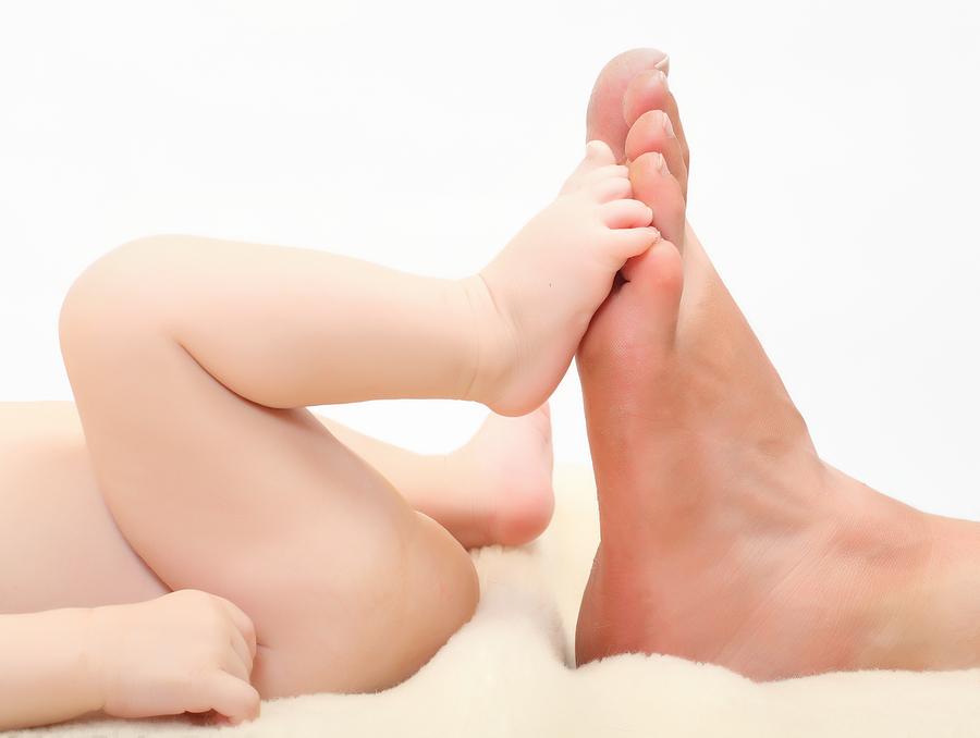 Babyvoet met grotere voet moeder