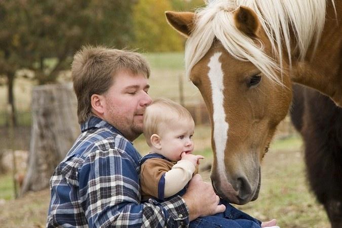 Vader met baby op kinderboerderij