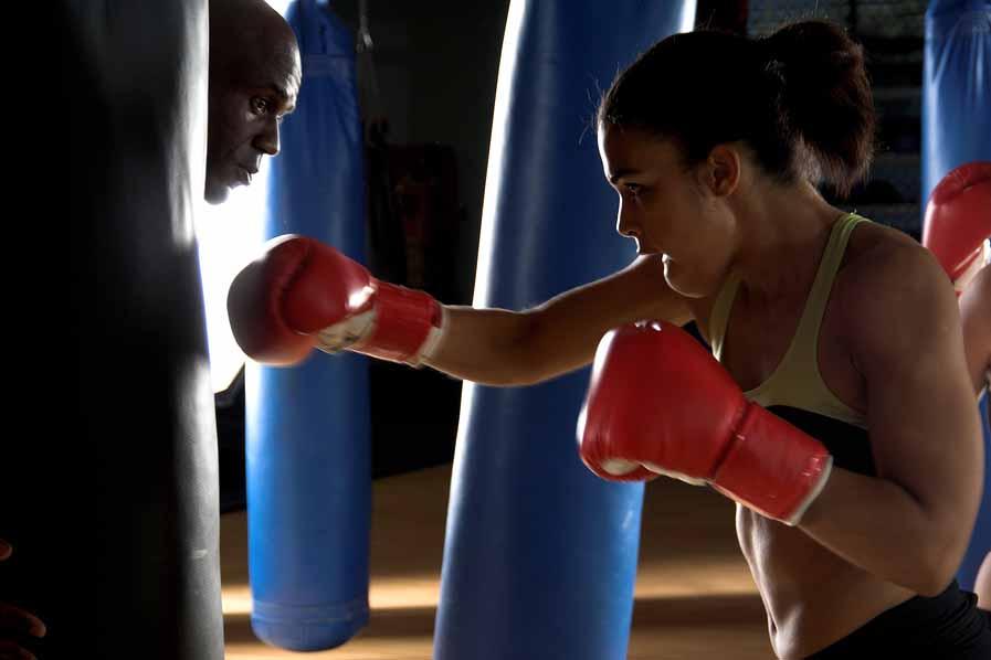 Vrouw bokst op bokszak om weer op gewicht te komen