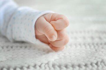 babygebaren van een pasgeboren baby die zijn handje tot een vuist maakt