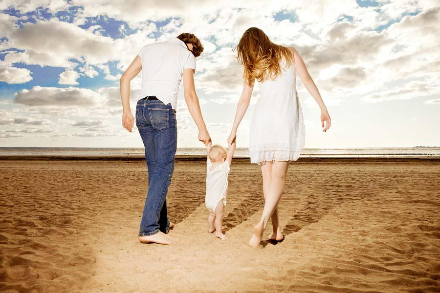Een baby doet haar eerste stapjes op het strand