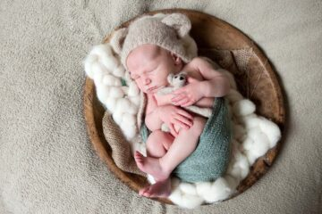 Newborn fotoshoot - baby met mutsje op in een mand
