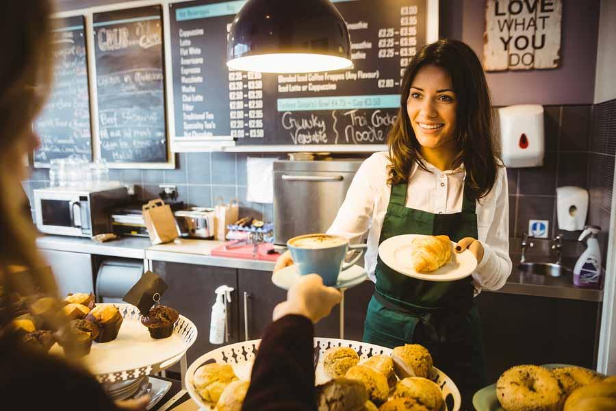 Zwangere vrouw serveert koffie in een café